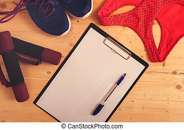 Weights, sneakers, sports bra, clipboard with pen
