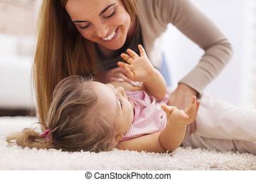 weinig moeder, meisje, hartelijk, spelend, tapijt