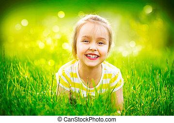 weinig; niet zo(veel), groene, verticaal, het glimlachen, gras, meisje, het liggen