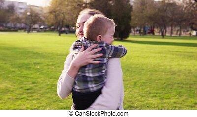weinig; niet zo(veel), haar, moeder, park, zoon, ondergaande zon , omhelzingen, whirls, vrolijke