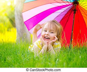 weinig; niet zo(veel), paraplu, kleurrijke, groene, onder, verticaal, het glimlachen, gras, meisje, het liggen