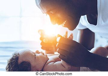 weinig; niet zo(veel), zijn, aanzicht, jonge, bed, bovenkant, spelend, terwijl, man, afrikaan, baby, het glimlachen, everything!, mijn, u, het liggen, vrolijke