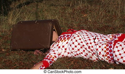 Weird Woman In White Dotted Gown Lying On Meadow With Suitcase On Head At Nature