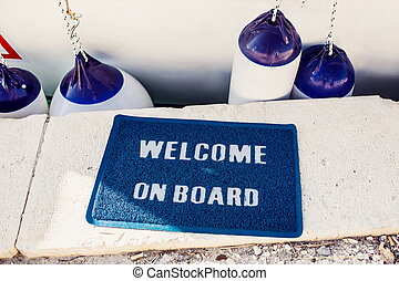 Welcome aboard mat on yacht in marina