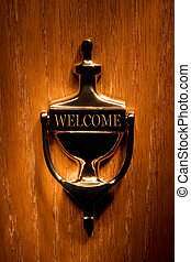 Welcome - Brass door knocker on a wooden door.