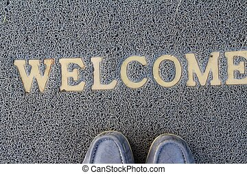 Welcome door mat on background and texture
