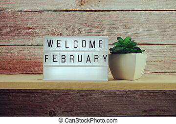 Welcome February word in light box on wooden shelves background