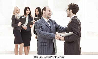 welcome handshake Manager and client on the background of business team