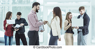 welcome handshake Manager and the client in the lobby of the office