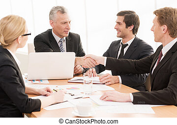 Welcome on board! Four business people sitting at the table while two of them shaking hands and smiling