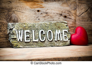 Welcome. - On the wood background of a plaque with an...