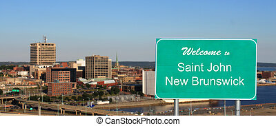 Welcome to Saint John, New Brunswick sign with city panorama in the background on a sunny day