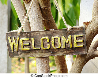 welcome sign hanging in the garden