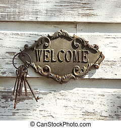 Welcome sign on wall. - Welcome sign and metal keys on old...