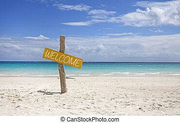 Yellow welcome sign on a tropical beach