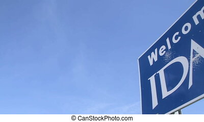 """Low angle pan to and from a blue """"Welcome To Idaho"""" sign placed along the highway."""