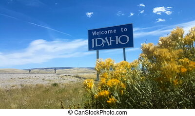 """Wide angle static shot of a blue """"Welcome To Idaho"""" sign placed along the highway."""