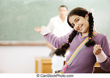 Welcome to my school: adorable schoolgirl smiling in classroom and teacher behind her