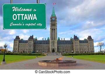 Welcome to Ottawa sign with Parliament building blurred in...