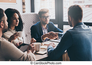 Welcome to our team! Two men shaking hands and looking at each other while their coworkers sitting at the business meeting