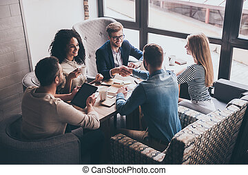 Welcome to our team! Two men shaking hands and looking at each other with smile while their coworkers sitting at the business meeting