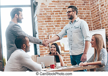 Welcome to our team! Two men shaking hands and smiling while their coworkers sitting at the table in office
