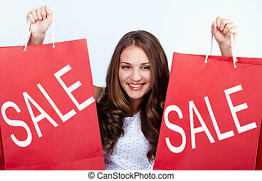 Welcome to sale - Happy girl holds red paperbags with symbol...