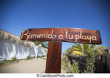 Welcome wooden sign post at the beach of Mancora