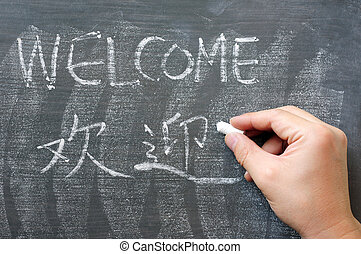 Welcome - word written on a blackboard with a Chinese...