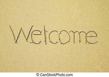Welcome written on sand at the beach