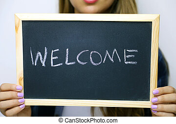 Welcome written on the blackboard holding by young unidentified woman.