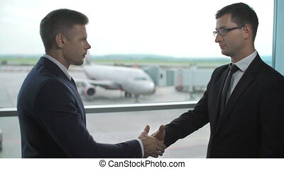 Two business men introducing themselves with a handshake standing at the airport panoramic window