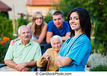 Confident and kind doctor welcoming the family members of the elderly patient.
