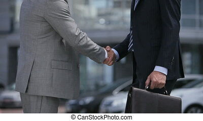Business people shaking hands and moving towards the office building