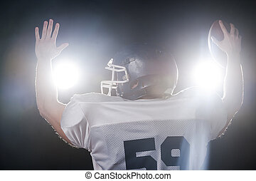 Welcoming stadium.  Rear view of American football player holdin