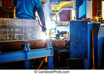 Welded steel workers - Steel plant workshop, workers are...