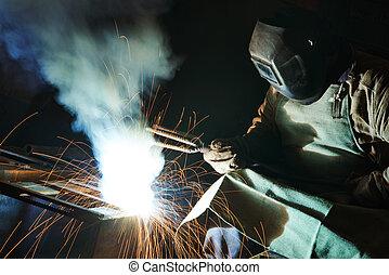 welder at factory workshop - welder working with electrode...
