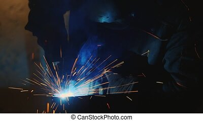 Welder at work. Many spectacular sparks and molten metal