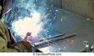 Welder at work welding a metal part - welder is welding...