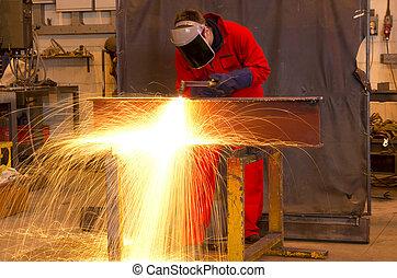 Welder bends to cut metal beam.