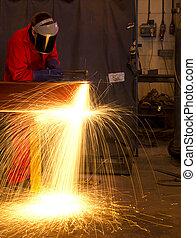 Welder bends to cut metal beam with orange sparks. - Welder...