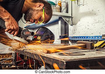 welder grinds metal angle grinder in workshop