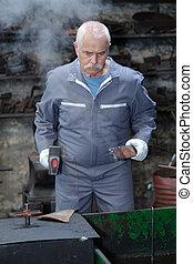 welder holding a hammer