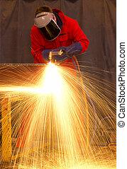 Welder in red creates huge  orange sparks