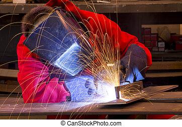 Welder in red overalls creates sparks.
