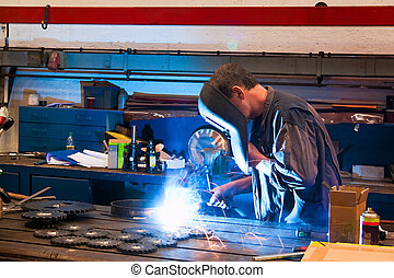 Welder in the workshop in the metal industry