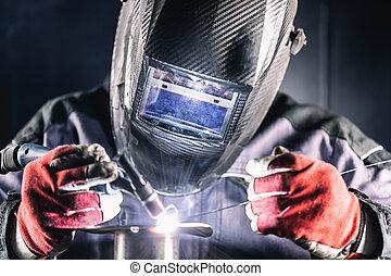 Welder industrial worker welding with argon machine