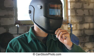 Welder opens mask and looking at camera. Portrait of...