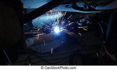 Welder repair the cars. Worker welding in the garage.