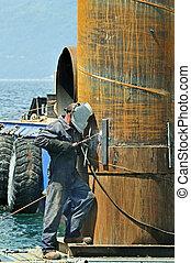 Welder - Worker using soldering iron on a rusty pylon in a...